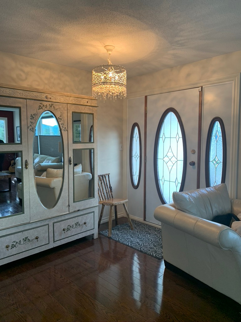 Entry Way with Oversized White Armoire and Ornate Chandelier