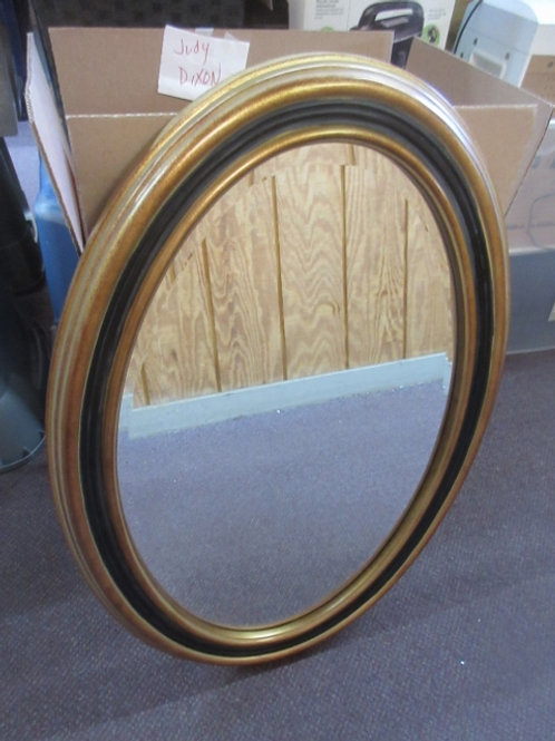 Oval beveled mirror in gold and black frame