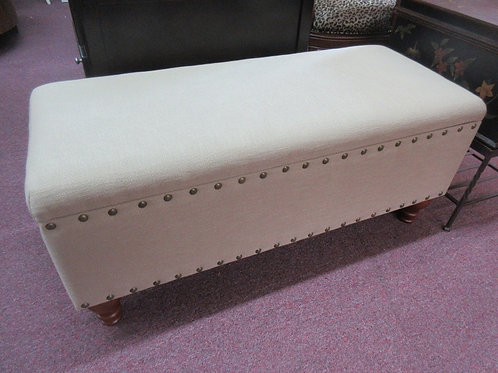 Tan upholstered footed storage bench with nail head accent