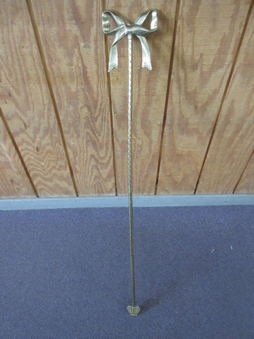 Decorative gold staff with bow on top