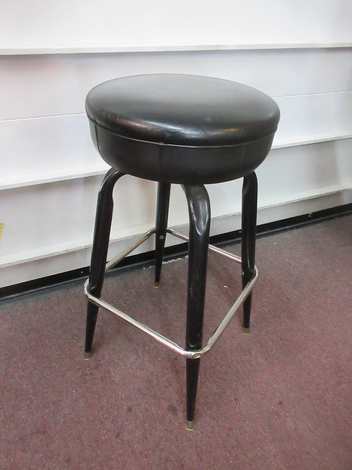 "Black stool with chrome foot rests & black vinyl swivel seat, 31""high"