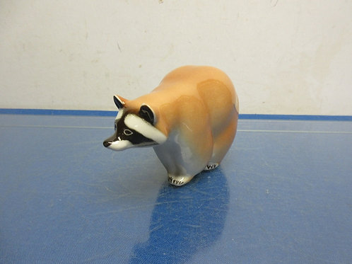 Ceramic statue of a racoon standing on all 4 legs