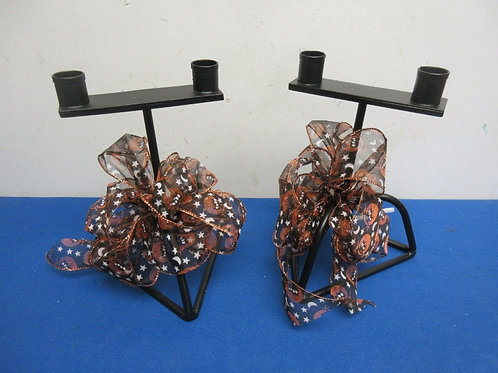Pair of black metal double taper candle holders with halloween bows