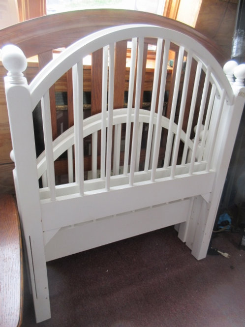 White arched spindle style twin bed with side rails, and slats