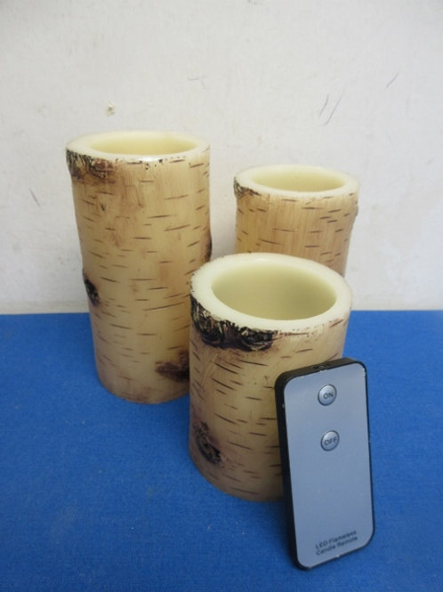 Set of 3 pillar candles that resemble tree bark, w/ remote/ needs batteries.