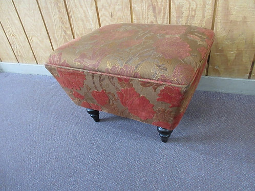 Orange tone upholstered footed ottoman