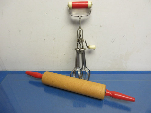 Wooden red handle rolling pin and a hand crank egg beater