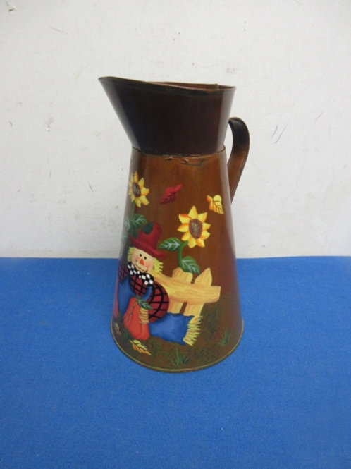 Small metal pitcher with scarecrow design