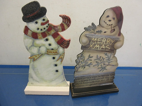 Pair of wooden cutout snowmen on wood stands