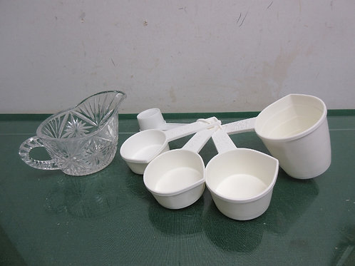 White plastic measuring cups and plastic creamer