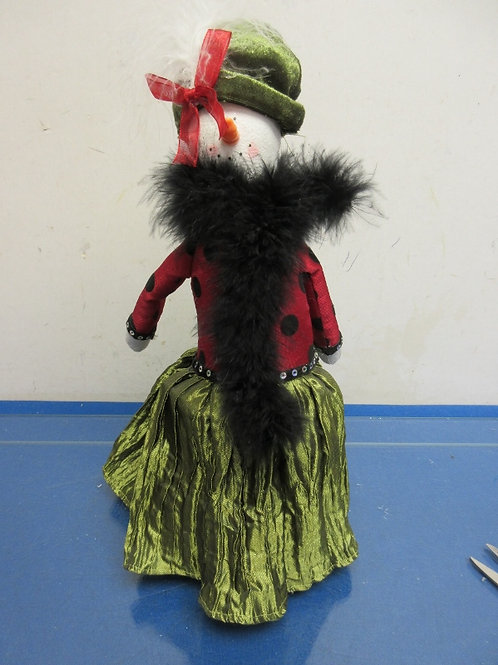 Standing snowman with red and green dress and fancy hat