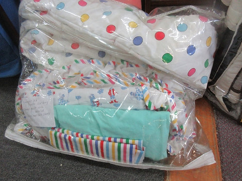 Clear plastic bag full of lightly used bby items, bumper pad, sheets, quilt and