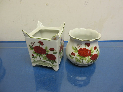 Pair of small white vases with red flowers, one round & one square