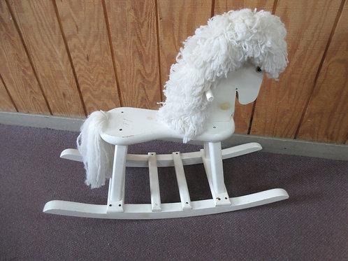 White wooden rocking horse with white mane
