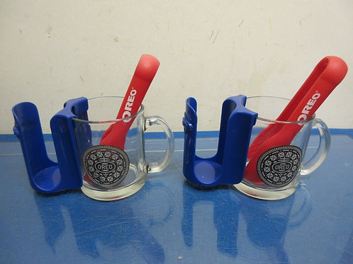 Pair of Oreo milk mugs with Oreo holders and red tongs for dipping