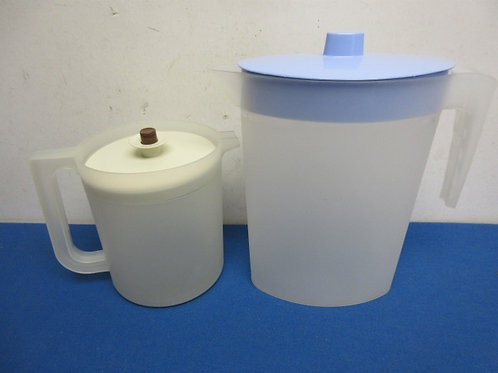 Pair of small plastic pitchers with lids