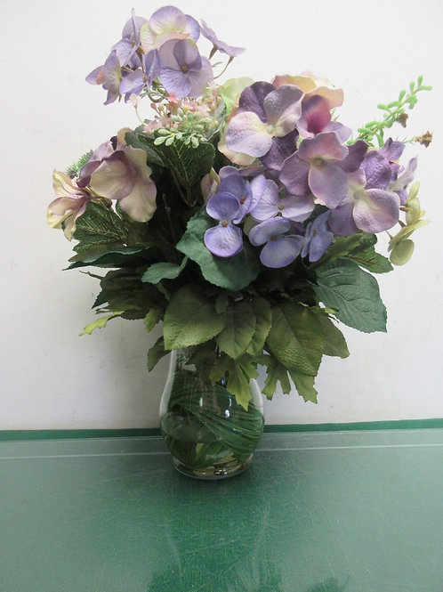 Purple and violet artificial flowers in vase