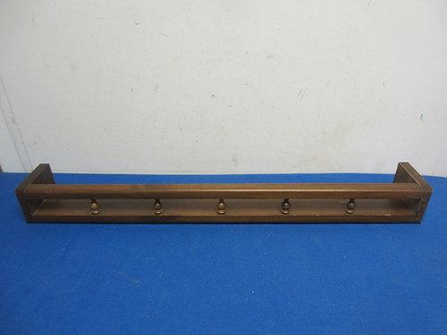 Narrow wooden wall shelf with rail around shelf