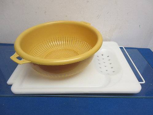 Over the sink cutting board and large plastic strainer