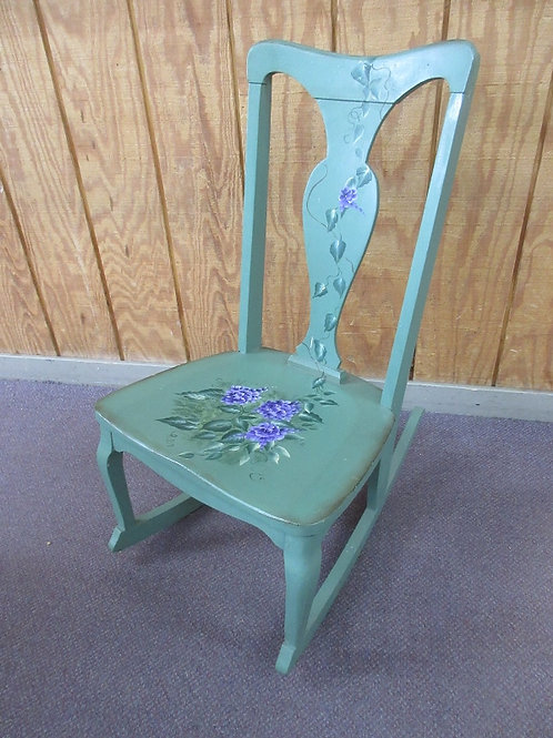 Green painted armless rocking chair with lilac flowers painted on seat