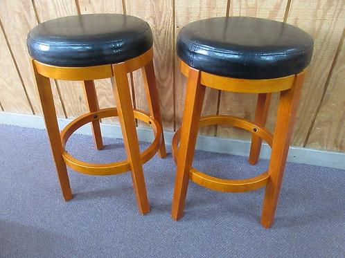 Pair of maple round stools with black vinyl seats