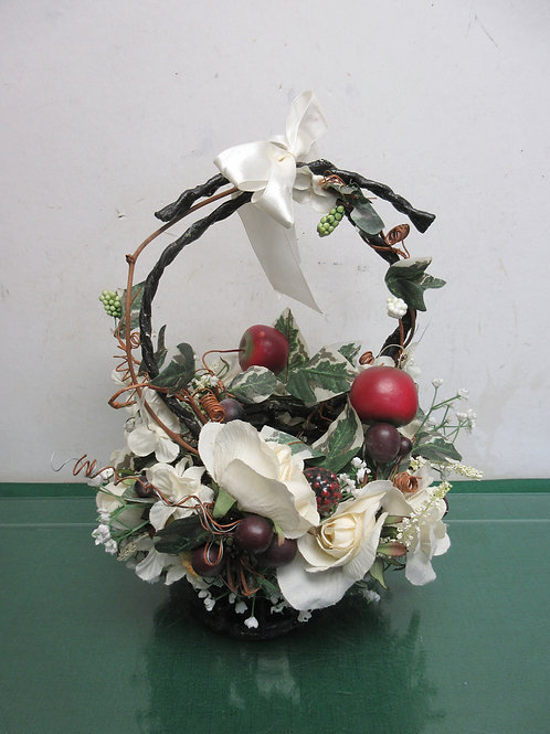 Dark wicker basket decorated with white flowers and fruit
