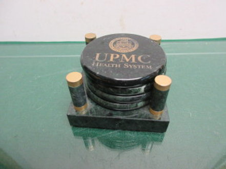 Set of 4 green marble UPMC coasters on a marble stand