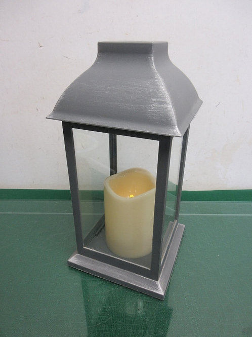 Gray lantern w/battery pillar candle, one corner is Chipped