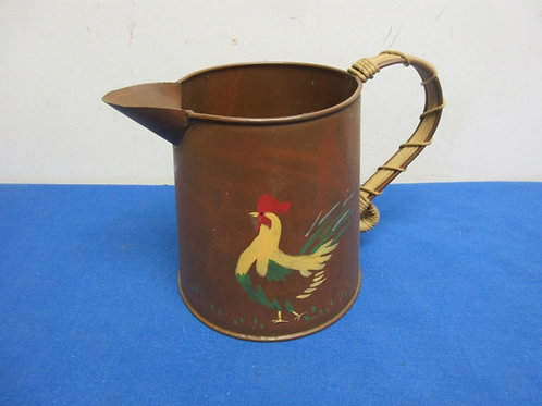 Copper tone metal pitcher with woven wicker over handle