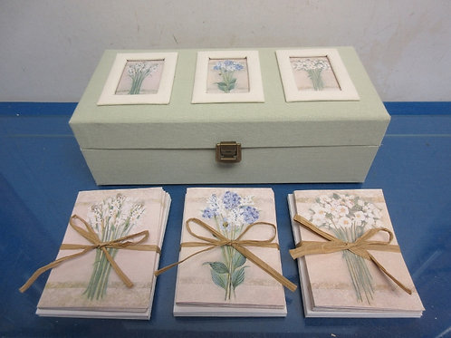 Mint green hinged box with floral design on lid, filled with note cards and enve