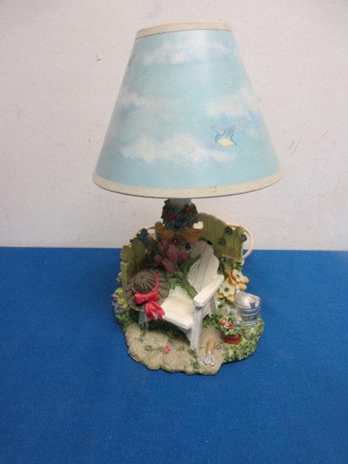 Small table lamp-base is a resin garden scene, has blue sky shade