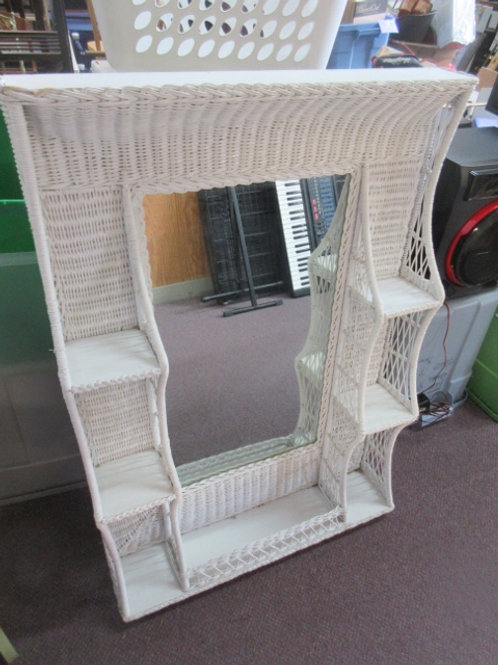 White wicker framaed mirror with 6 small shelves on sides, stands on dresser