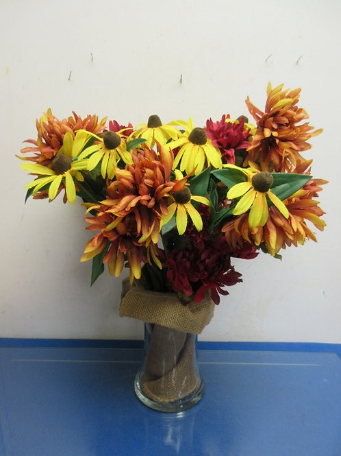Large fall floral arrangement in glass vase with burlap