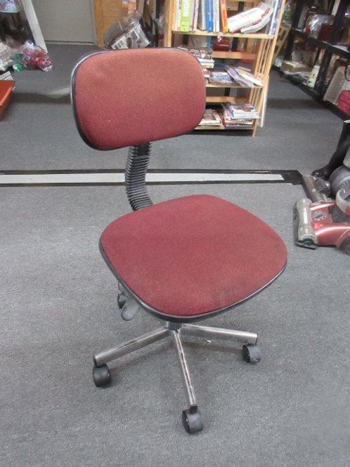 Burgundy armless desk chair on wheels