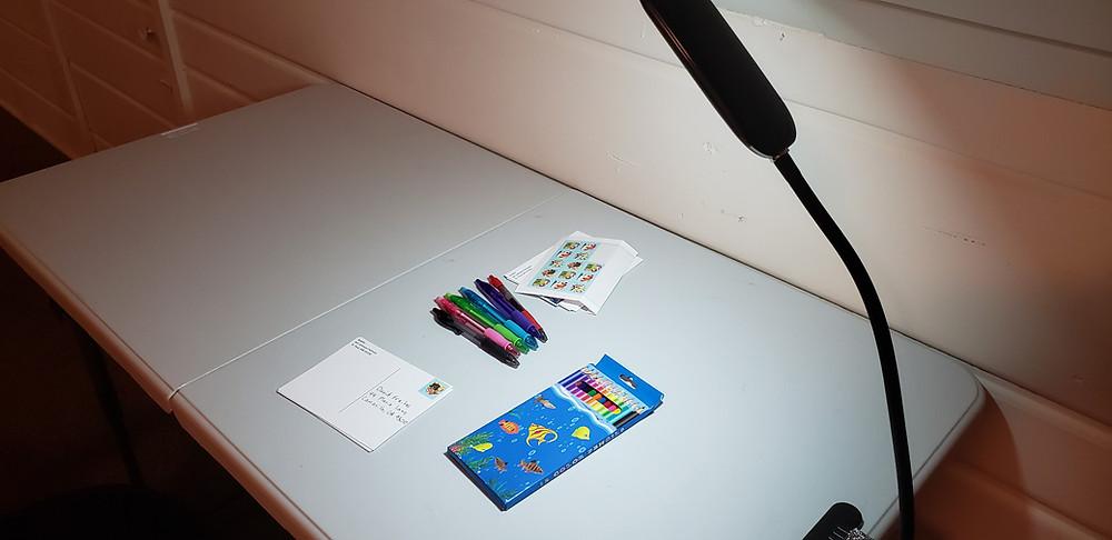 Postcard Writing Supplies Under a Lamp.
