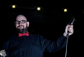 Comedian Dan Bublitz Jr in a bowtie holding a microphone