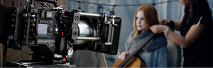Woman with red hair sitting in front of a Panvision camera