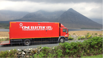 Large Red Truck traveling in the mountains with Cine Electric written on the side