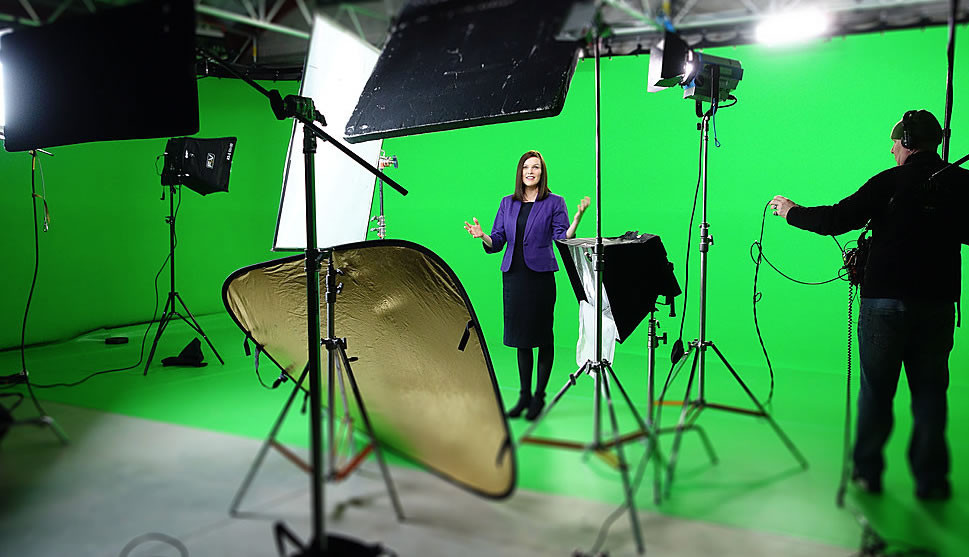 Woman standing in front of a green screen in a film studio