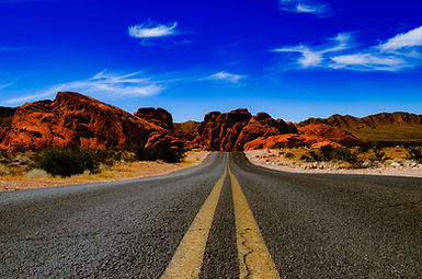 Two-lane road surrounded by desert mountains with blue sky