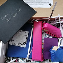A box of shredded paper with four wrapped gifts and a wrapped book, as well as a spoilers envelope.