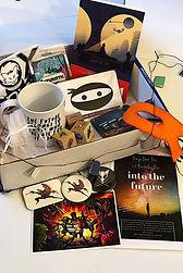 a box containing badges, a mug, 2084 book, a ninja mask, book decorations & more.