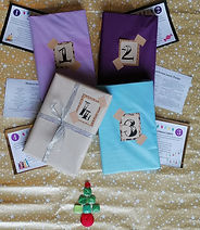 Four books wrapped in colourful paper and number 1-4, with recipe cards and numbered cards with advent traditions peeking out from behind.