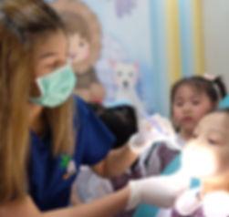Drg. Tri Soehartini sedang memeriksa gigi anak-anak.