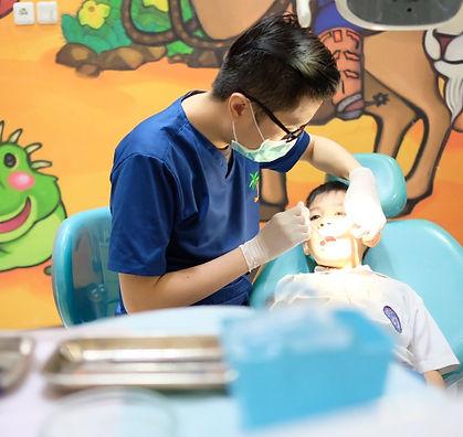 Drg. Agus sedang memperbaiki gigi seorang anak yang mengalami kerusakan.