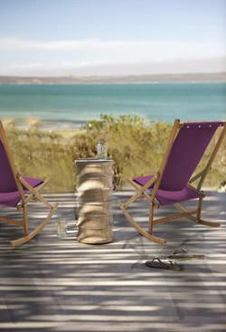 Beach rocking deck chairs under tree