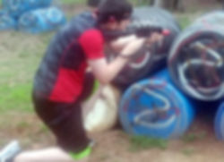 A boy hiding behind barrels playing laser tag
