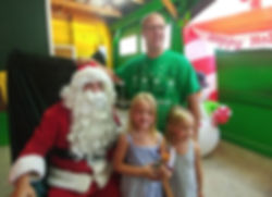 a father and his two young daughters standing next to Santa Clause