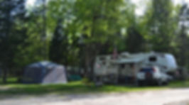 A camper in a camp site that has water, sewer, and 30 amp electric