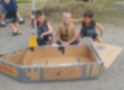 three boys gathered around a home made cardbord boat